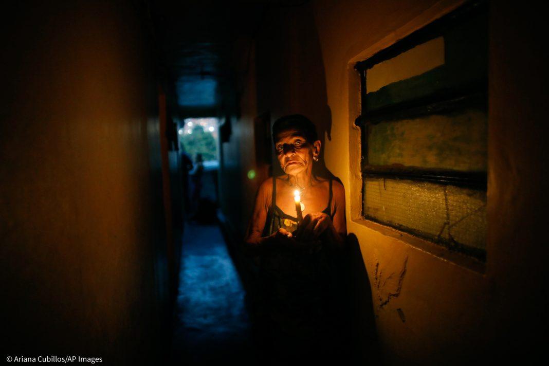 Mulher segurando vela em corredor escuro (© Ariana Cubillos/AP Images)