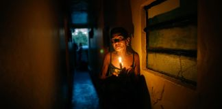 Woman holding candle in dark corridor (© Ariana Cubillos/AP Images)