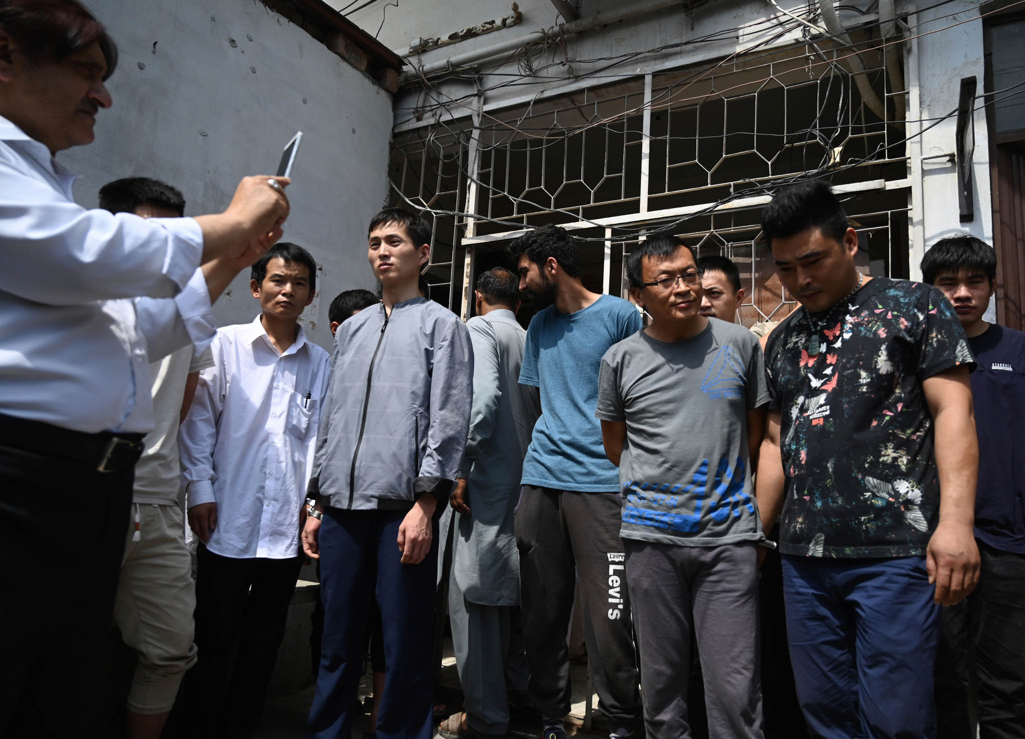 Man taking picture of other men (© B.K. Bangash/AP Images)