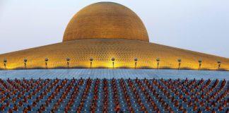 اپنے بڑے مندر کے سامنے لائنوں میں بیٹھے ہوئے بدھ بھکشو۔ (© Sakchai Lalit/AP Images)