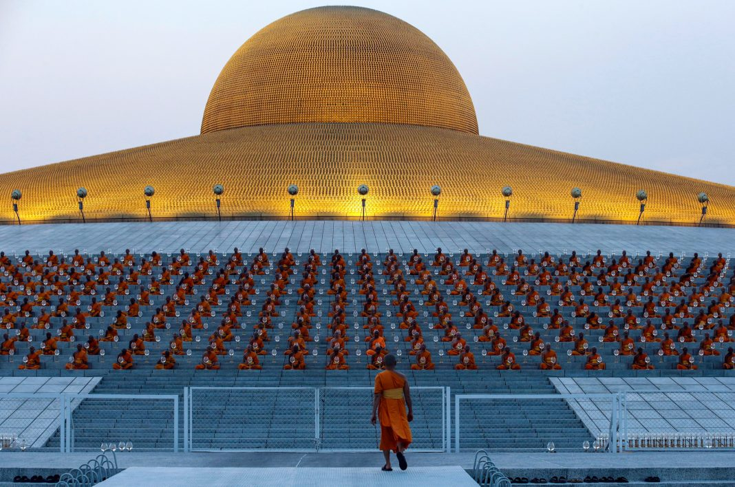 Monks lined up in formation in front of temple (© Sakchai Lalit/AP Images)