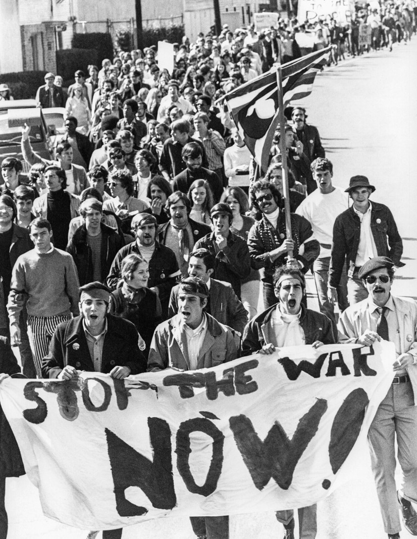 """Line of marchers with """"Stop the war now!"""" sign (© AP Images)"""