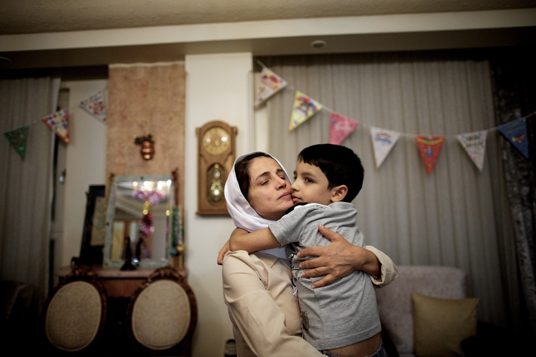 Mulher abraçando menino (© Behrouz Mehri/AFP/Getty Images)