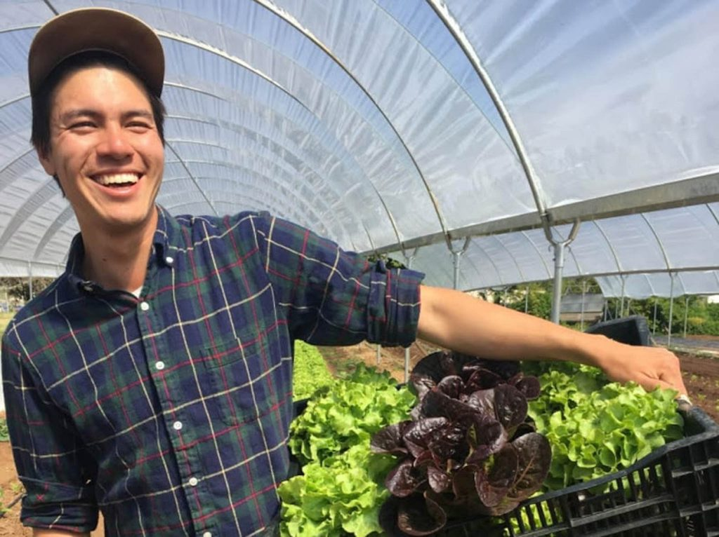 Smiling man in greenhouse holding basket of produce (Courtesy Scott Chang-Fleeman)