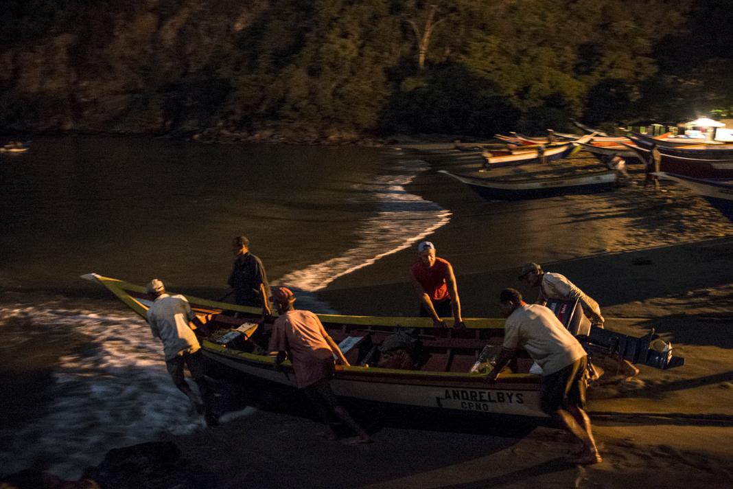 Men pushing a boat into water at night (© Carlos Garcia Rawlins/Reuters)