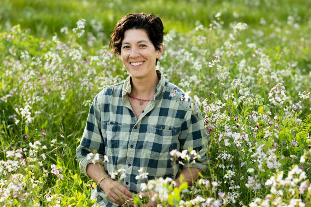 Smiling woman standing in field (© Paige Green)