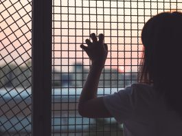 Young woman shown from behind with hand on fencing (© structuresxx/Shutterstock)