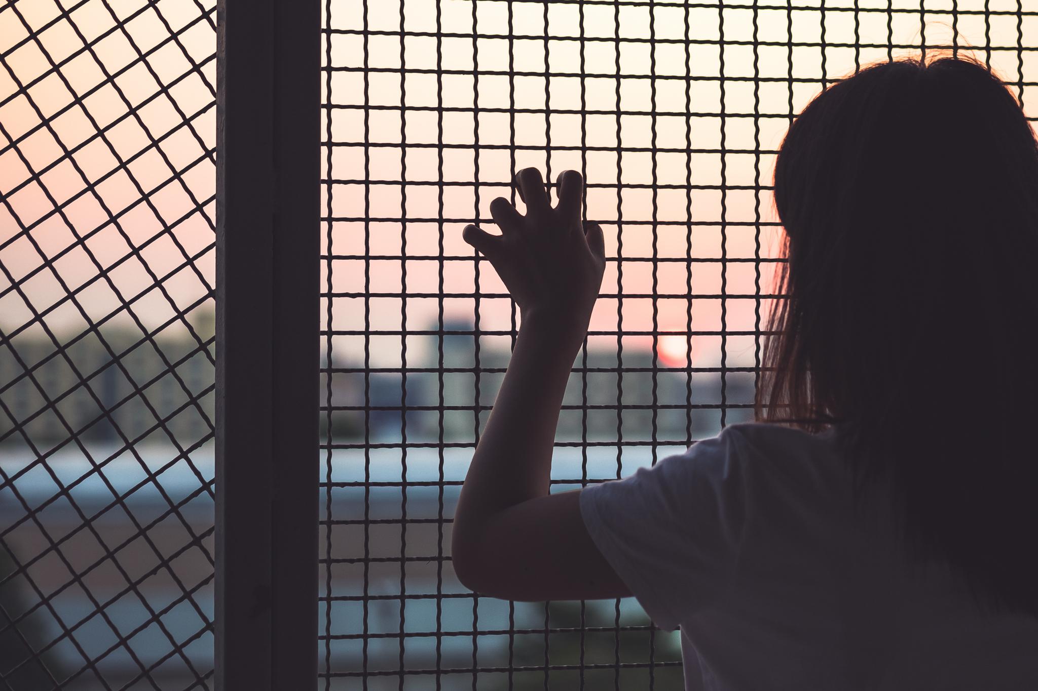 Joven mujer vista de espaldas con una mano en una cerca (© structuresxx/Shutterstock)