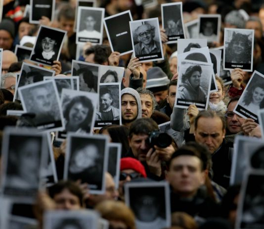 A crowd of people holding up pictures (© Natacha Pisarenko/AP Images)