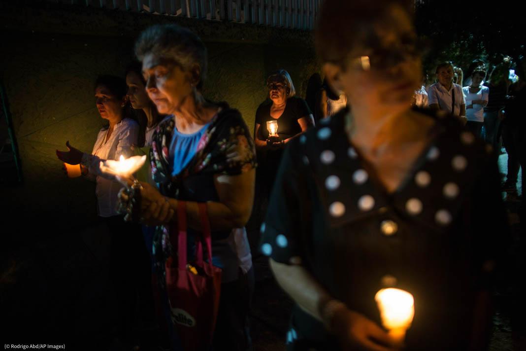 Personas sosteniendo velas (© Rodrigo Abd/AP Images)