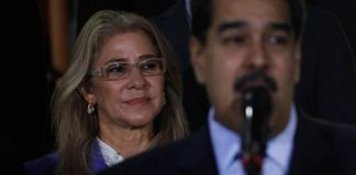 Nicolás Maduro speaking into microphone with Cilia Flores standing behind him (© Ariana Cubillos/AP Images)