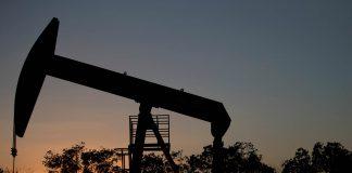 Oil pump silhouetted against sun (© Fernando Llano/AP Images)