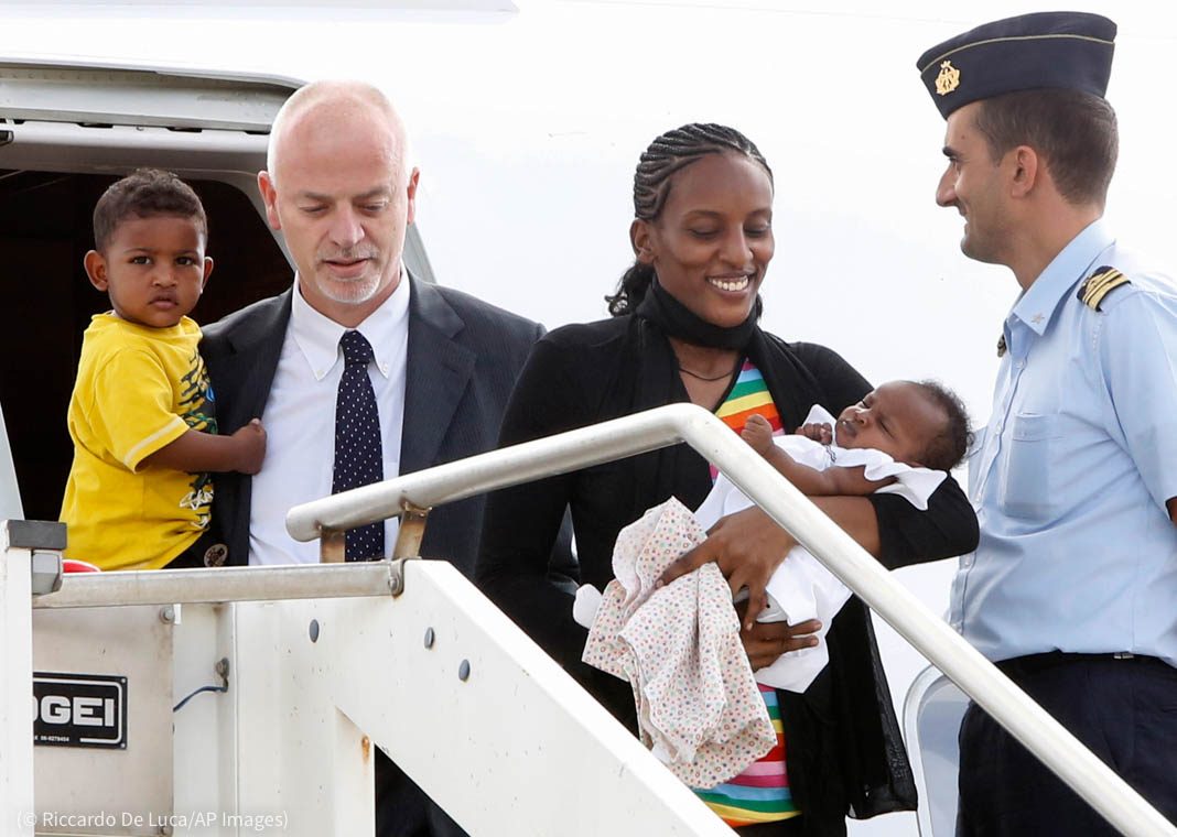Man and woman carrying children leaving aircraft (© Riccardo De Luca/AP Images)