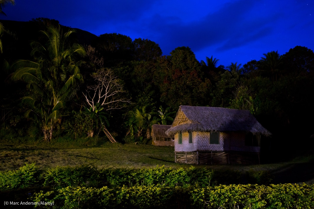 Small thatched-roof house at night (© Marc Anderson/Alamy)
