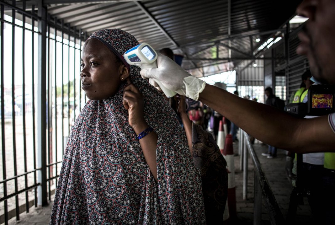 Woman having her temperature taken (© John Wessels/AFP/Getty Images)