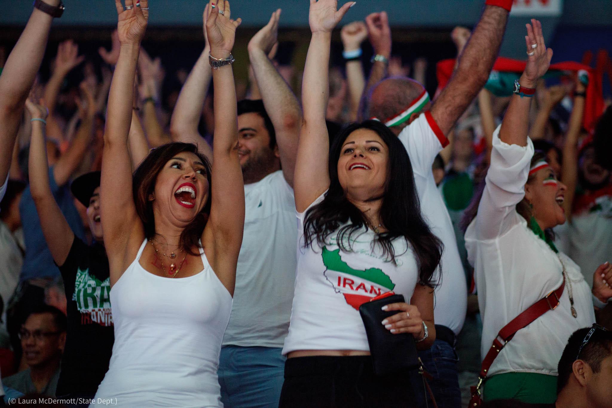 Gran grupo de hinchas vitoreando con los brazos alzados (© Laura McDermott/Depto. de Estado de EE. UU.)