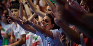 Mulher com a bandeira iraniana pintada no rosto em meio à multidão de torcedores (© Laura McDermott/Depto. de Estado)