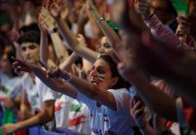Woman with Iranian flag painted on cheek amid crowd of cheering fans (© Laura McDermott/State Dept.)