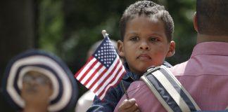 多米尼加移民卡布雷拉抱着孩子参加入籍仪式(照片:美联社)
