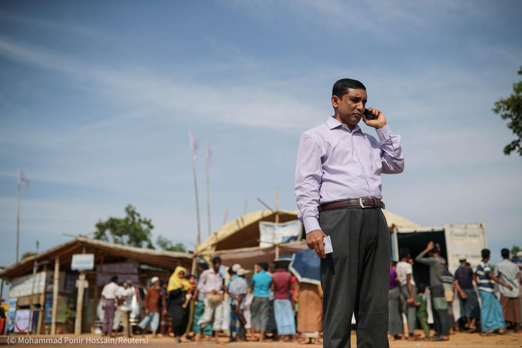 Man talking on mobile phone outside (© Mohammad Ponir Hossain/Reuters)