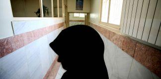 Person in headscarf standing in hallway of prison (© Morteza Nikoubazl/Reuters)