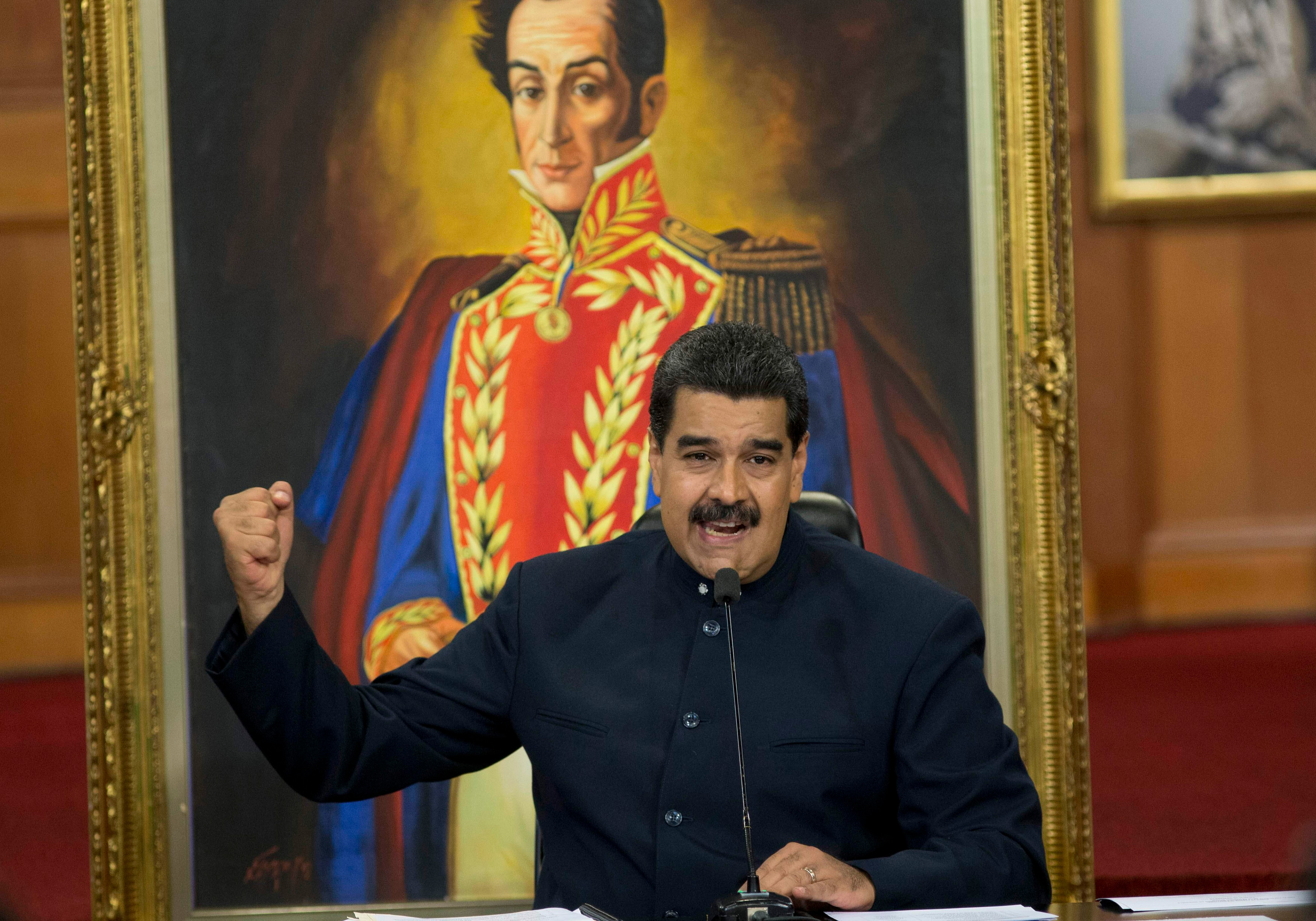 Man at microphone with fist raised, with large portrait of elaborately uniformed man behind him (© Ariana Cubillos/AP Images)