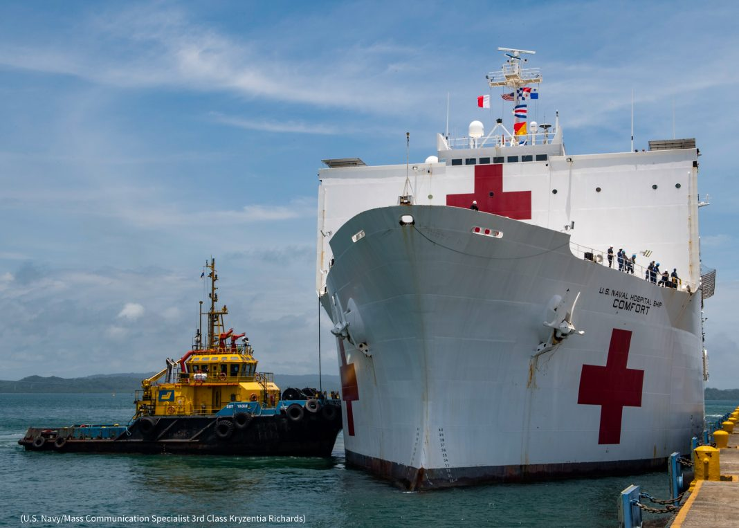 Large ship and small boat at dock (U.S. Navy/Mass Communication Specialist 3rd Class Kryzentia Richards)