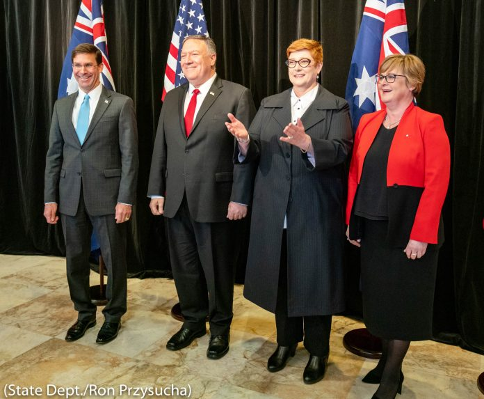 4 people standing in front of Australian and American flags (State Dept./Ron Przysucha)