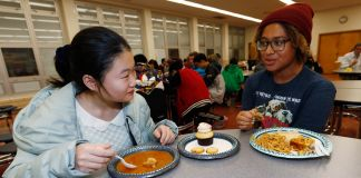 Students eating lunch in a cafeteria (© David Zalubowski/AP Images)
