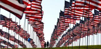 Two people between rows of U.S. flags (© Jae C. Hong/AP Images)