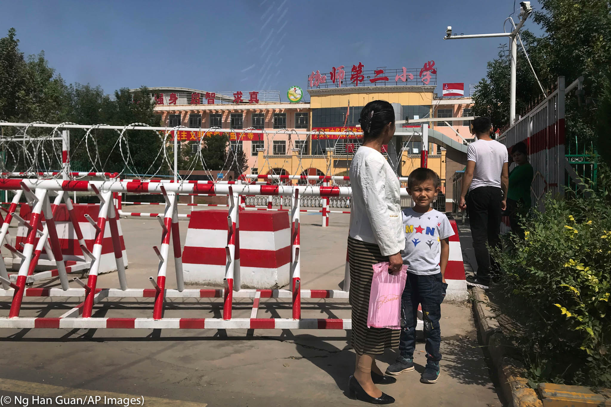Une femme et un enfant devant une école protégée par des barrières et des barbelés (© Ng Han Guan/AP Images)