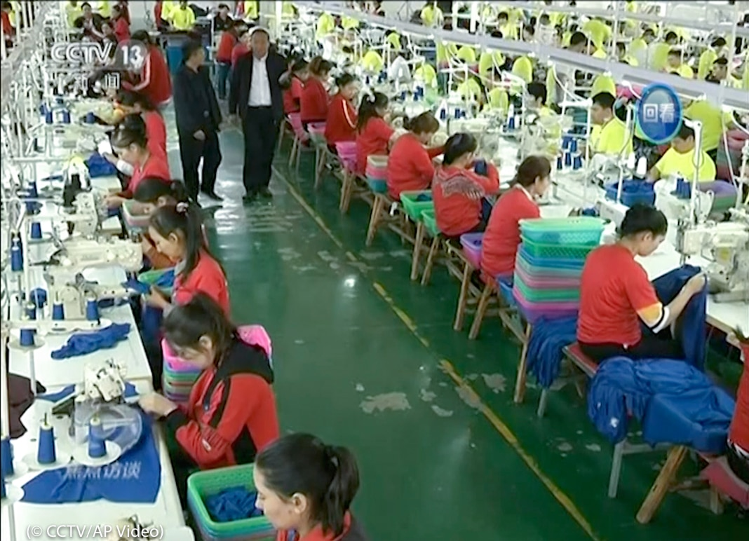 Long rows of people wearing matching clothes, seated and working (© CCTV/AP Video)
