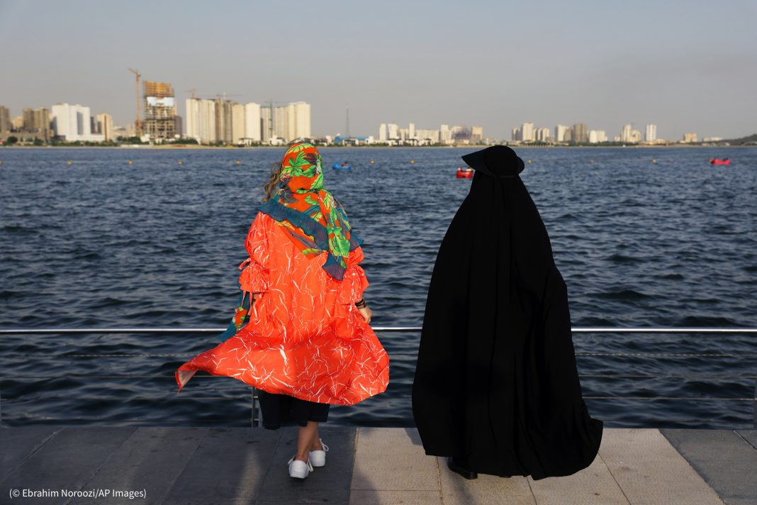 Two women with head coverings standing on dock overlooking water (© Ebrahim Noroozi/AP Images)