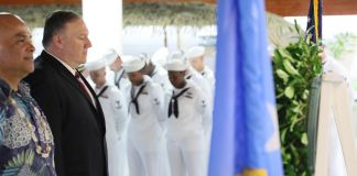 Rows of sailors and others at ceremony with flags (© Jonathan Ernst/AP Images)