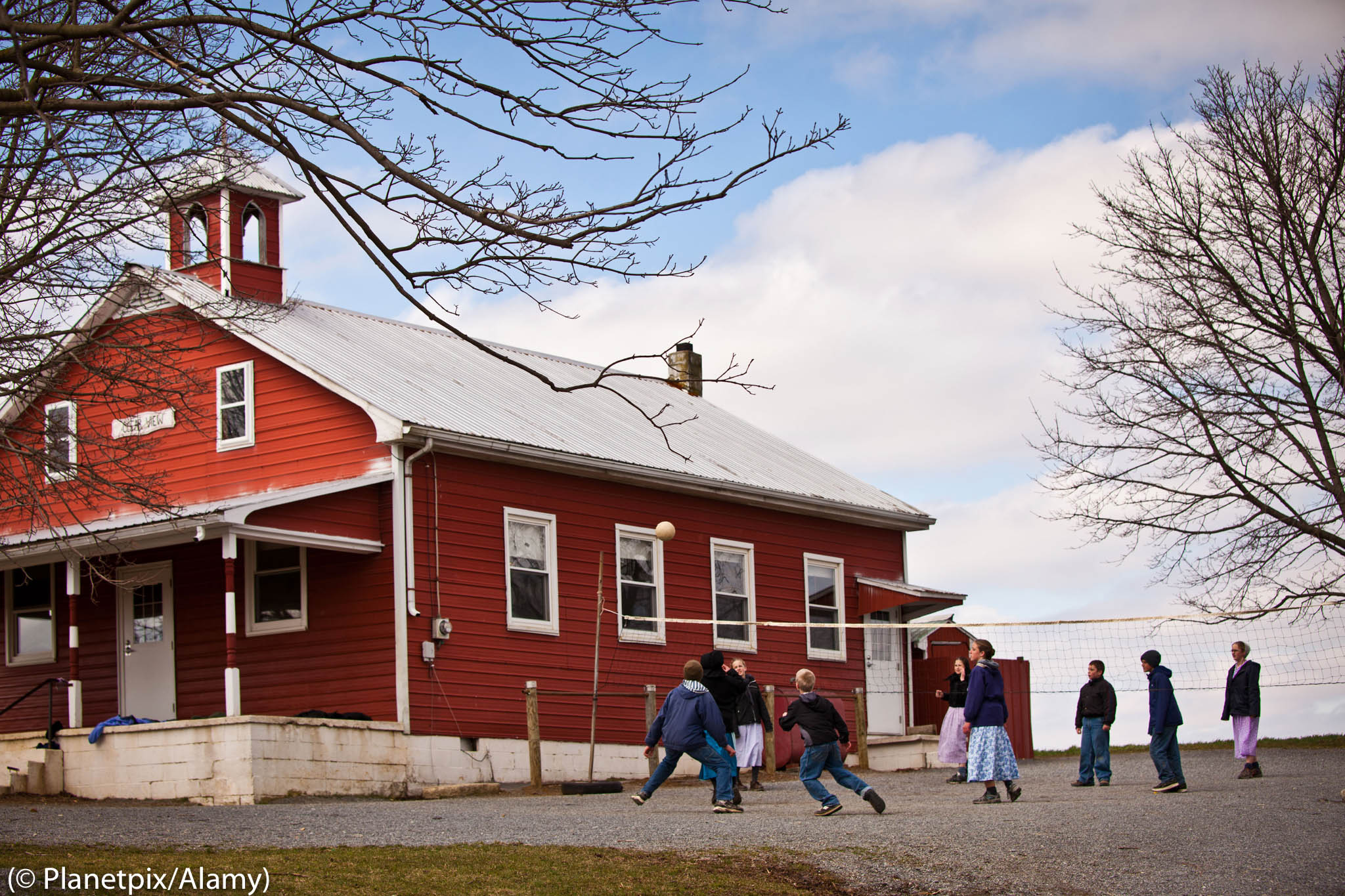 Amish children playing volleyball outside red schoolhouse (© Planetpix/Alamy)