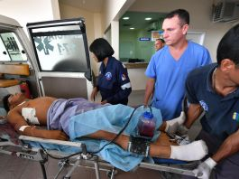 Медицинские работники оказывают помощь мужчине на каталке (© Nelson Almeida/AFP/Getty Images)