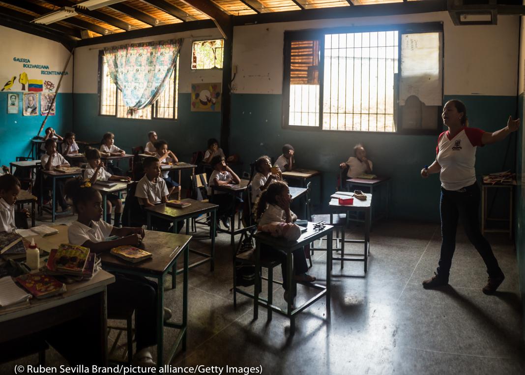 Teacher leading students at desks in darkened classroom (© Ruben Sevilla Brand/Picture Alliance/Getty Images)