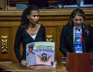 Two women presenting in an assembly hall, one holding a small poster (© Rafael Briceño Sierralta/NurPhoto/Getty Images)