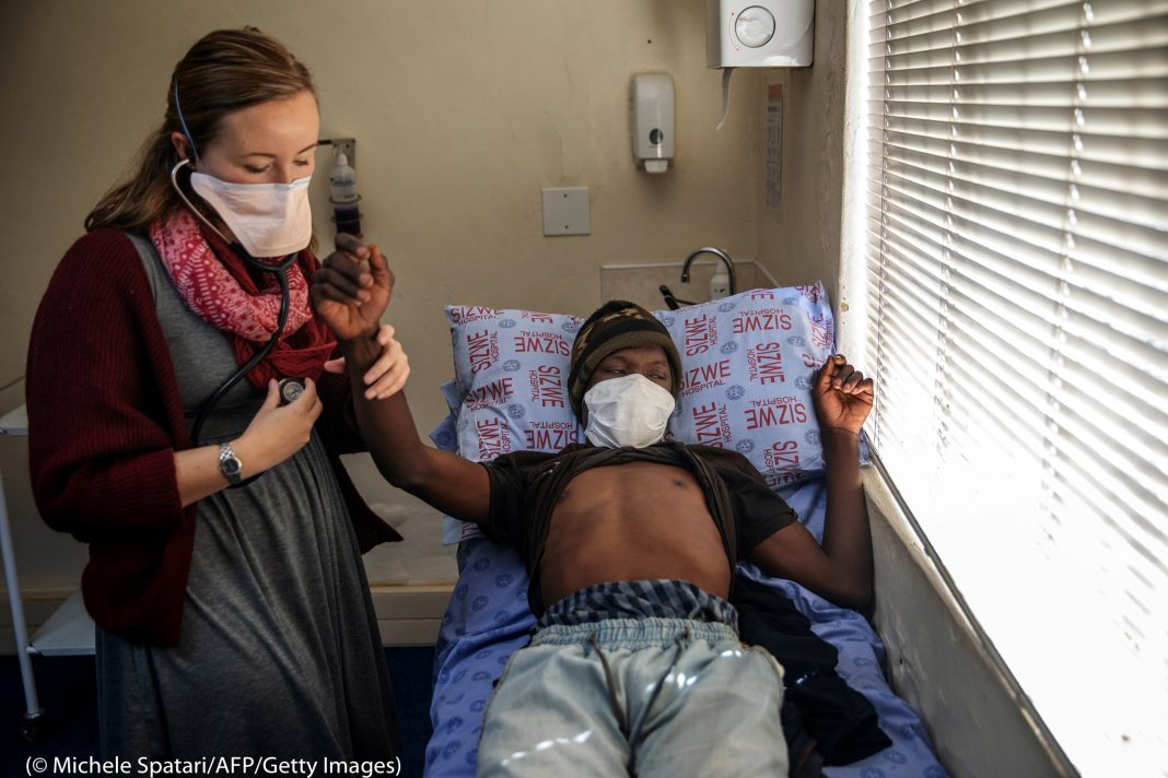 Woman in mask taking pulse of reclining man in mask (© Michele Spatari/AFP/Getty Images)