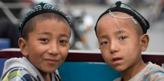 Two Uighur children with hats in China (© Eric Lafforgue/Art in All of Us/Corbis/Getty Images)