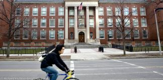 Man riding a bicycle in front of a school (© Michael Fein/Bloomberg/Getty Images)