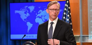 Man at lectern with flag and world map behind (State Dept./Michael Gross)