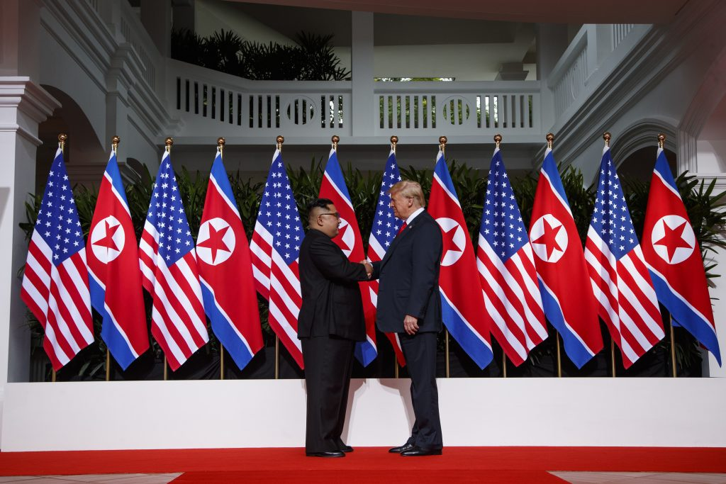 Kim Jong Un and Donald Trump shaking hands in front of row of flags (© Evan Vucci/AP Images)