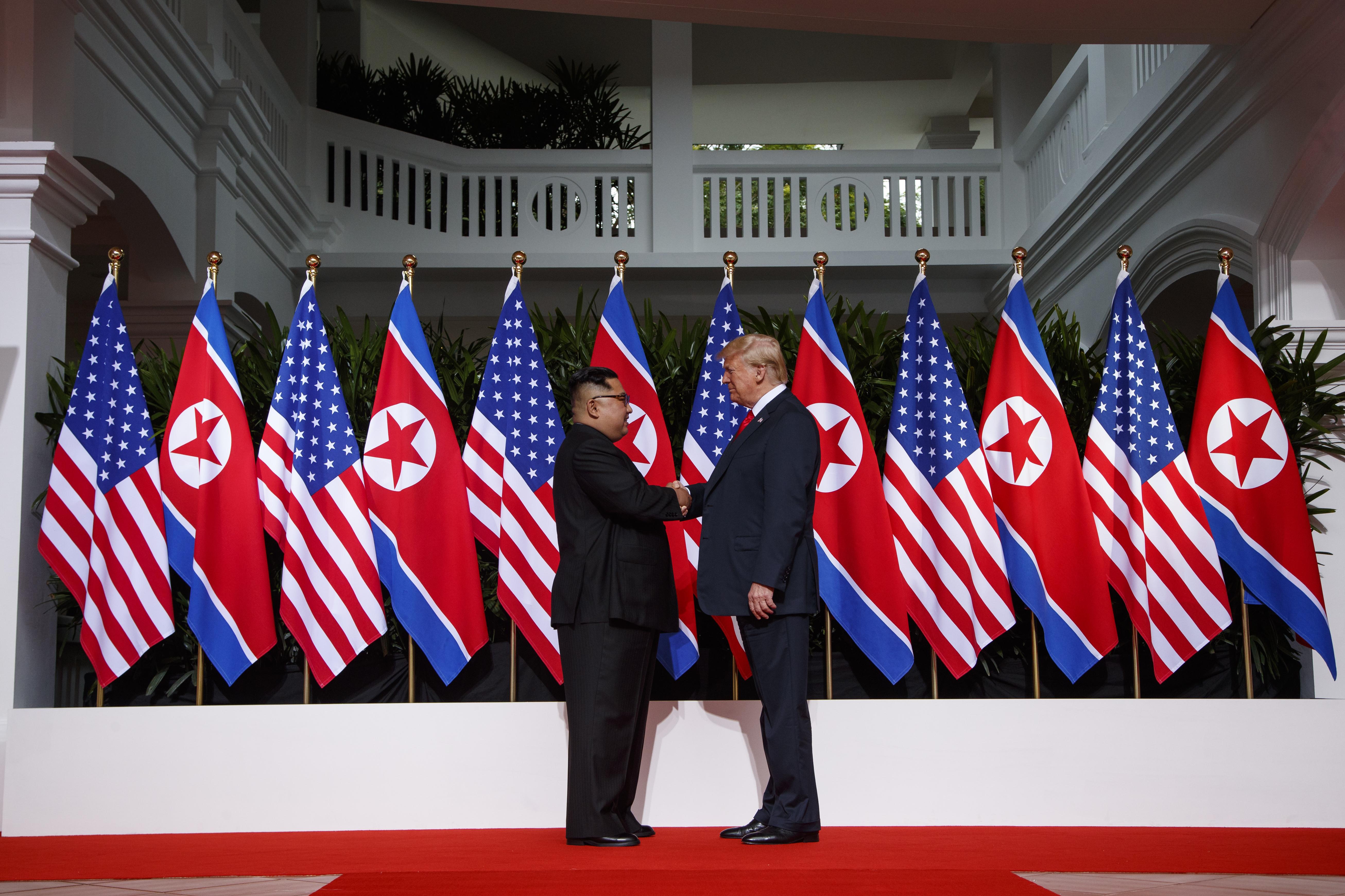 Kim Jong Un y Donald Trump se dan la mano frente a una fila de banderas (© Evan Vucci/AP Images)