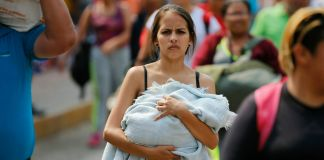 Woman carrying baby wrapped in a blanket in the street (© Fernando Llano/AP Images)
