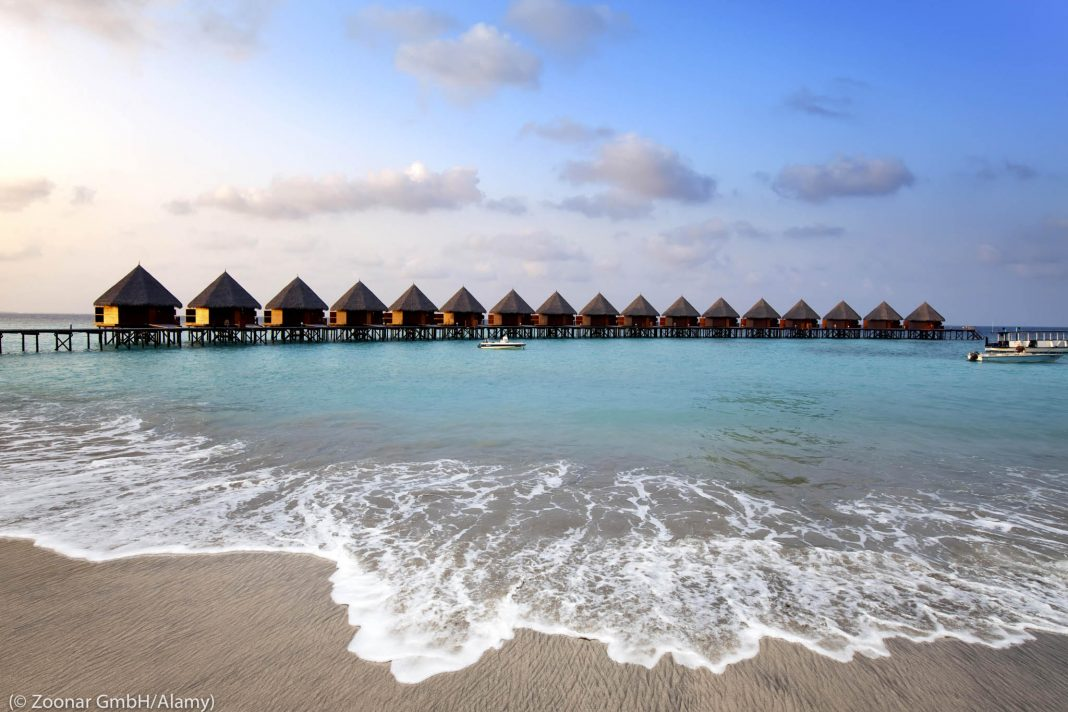 Houses on stilts in ocean seen from beach (©Zoonar GmbH/Alamy)