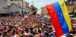 Large Venezuelan flag flying over a crowd (©Eva Marie Uzcategui/Getty Images)