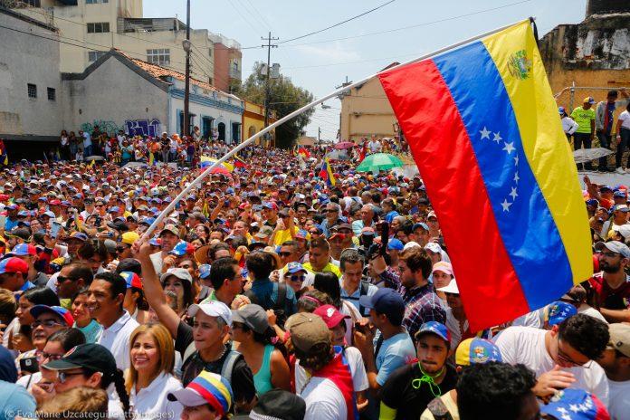 Enorme bandera de Venezuela ondea sobre una multitud (© Eva Marie Uzcategui/Getty Images)