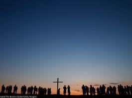 Silhueta de pessoas reunidas e grande cruz ao nascer do sol (© Jessica Rinaldi/The Boston Globe/Getty Images)