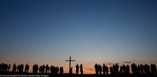 Line of people and large cross silhouetted at sunrise (© Jessica Rinaldi/The Boston Globe/Getty Images)